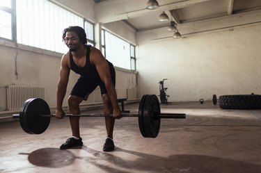 Man doing a deadlift with loaded barbell in a garage