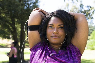 woman wearing a purple shirt and listening to headphones while doing a triceps stretch in a park