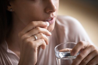 Close up young woman taking pill, holding water glass