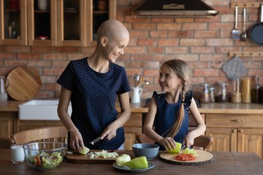 Happy sick mother cancer patient and little daughter cooking together