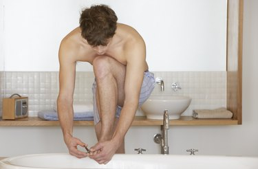 Young man leaning on bath cutting toenails to prevent ingrown toenail