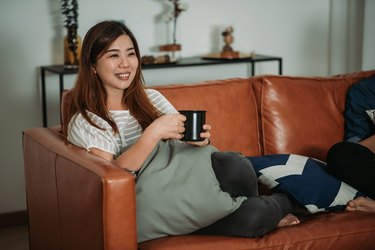 A woman watching TV and laughing as a way to promote heart heath