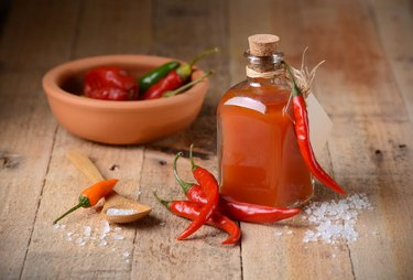 Capsaicin-rich tabasco peppers next to tabasco sauce in a bottle