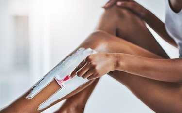 close view of a person shaving their legs with shaving cream to avoid razor burn