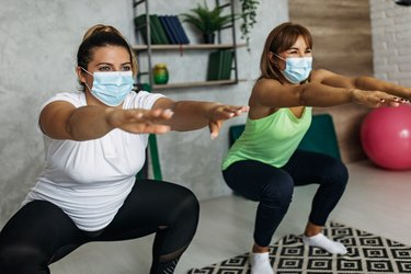 Friends wearing a mask while exercising together at home doing jump squats