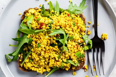 Tofu scramble toast with greens on rye bread, top view. Healthy vegan food concept.