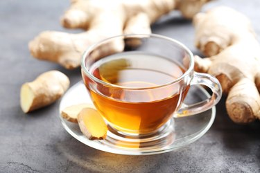 Cup of tea with ginger root on grey wooden table, as a natural remedy for cough