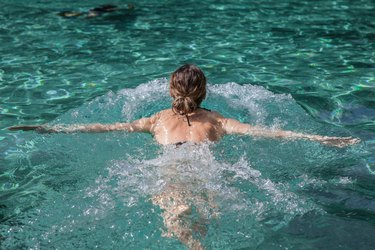 a young woman doing a swim cardio workout on top of pool water, back view