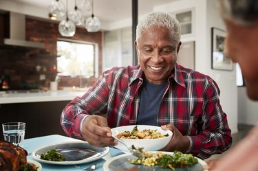 Older Couple Enjoying Meal Around Table At Home