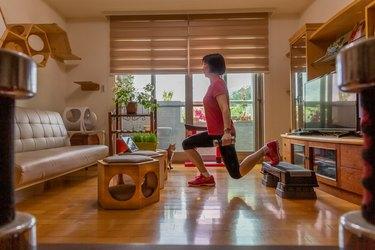 Woman performing Bulgarian split squat at home.