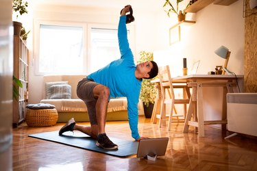 fit man doing a turkish get-up with a kettlebell in his living room at home