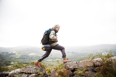 woman hiking outside with backpack to lower blood pressure