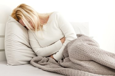 Young woman suffering from abdominal pain while sitting on bed at home