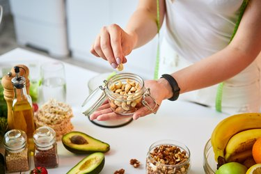 woman eating different nuts (cashew, hazelnut, almond) in modern kitchen. Healthy food and Dieting concept. Loosing Weight