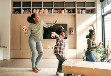Mother and kids dancing in the living room