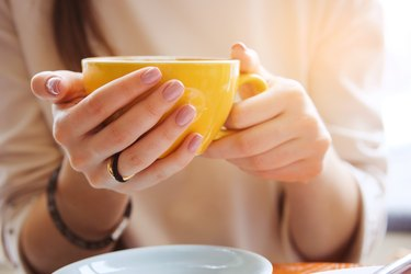 Yellow coffee mug in the hands of a young woman