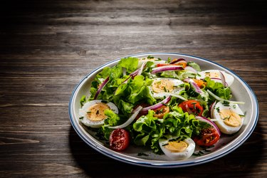 Boiled eggs and colorful vegetables on a white plate on wooden background