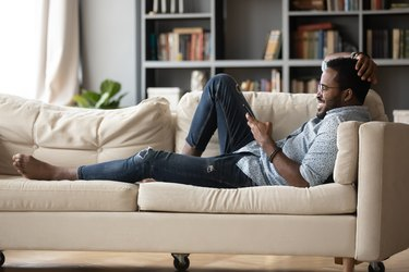 Relaxed young african ethnicity man using mobile phone.
