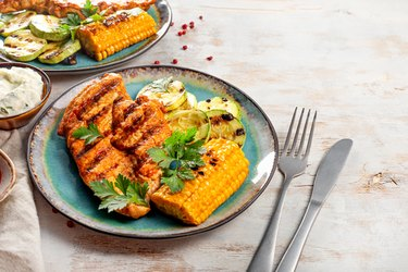 Grilled chicken breast with corn and zucchini on a blue plate top view. Summer dish with grilled chicken and vegetables on the white background