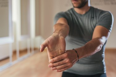 Sporty man stretching forearm before gym workout