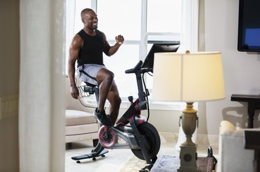 black man enjoying the benefits of stationary bike workouts at home in her living room