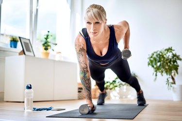 Athletic woman doing dumbbells exercise during home workout. Dombbell row.