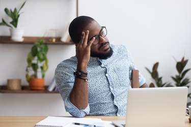 man sitting at his desk and feeling forgetful