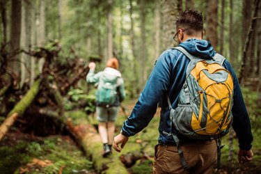 close-up shot of a man hiking in the woods with a yello backpack