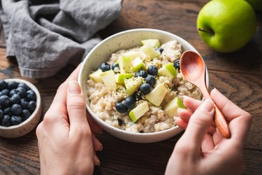 Bowl of oatmeal porridge with apple and blueberry
