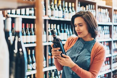 Young woman holding a bottle in the wine shop