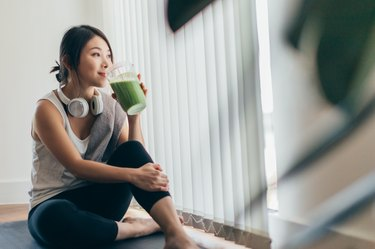 young woman drinking a smoothie after exercise, as a natural remedy for acid reflux