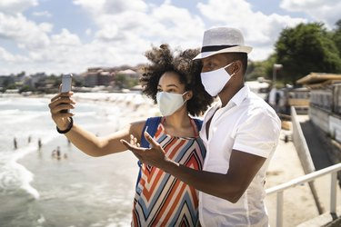 A couple wearing masks and taking a selfie near the beach