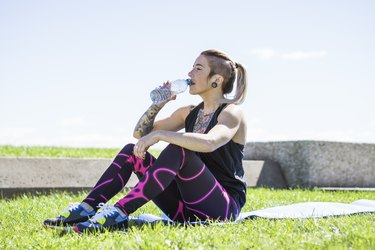 young exercising women resting on the grass and drinking water
