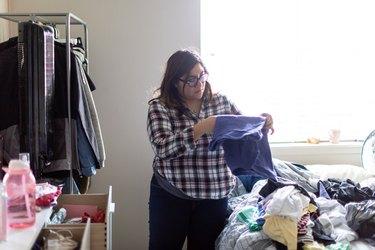 Hispanic Woman Folding Laundry at Home