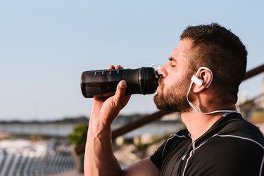 muscular man wearing earbuds and drinking a protein shake with leucine for muscle growth