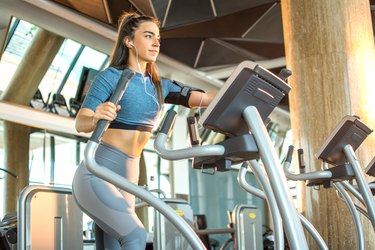 Attractive young fitness woman working out on an elliptical trainer in gym