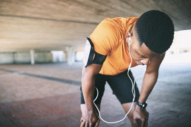 exhausted man taking a break to stop and breathe while running