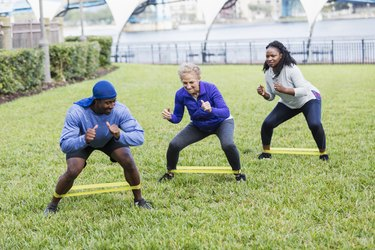 African American male trainer training senior women with resistance band standing glute exercises
