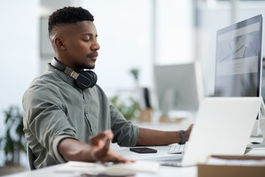 Young Black man meditating in at his desk at work at the best time of day to meditate
