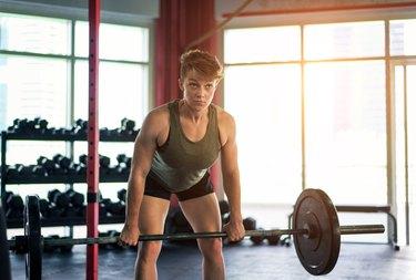 caucasian woman doing a barbell stiff-leg deadlift in the gym