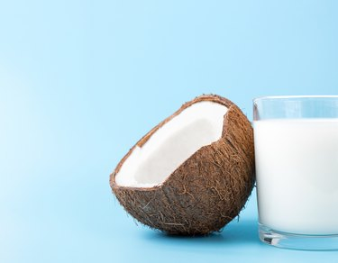 Coconut Milk in a glass and coconut on blue background with copy space