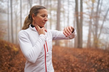 upper body woman taking her pulse after running in fog on cold autumn morning