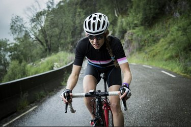 female race cyclist riding on a mountain road