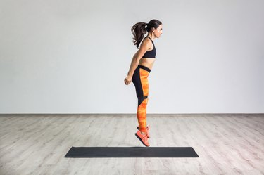 Side view portrait of young athletic healthy woman wearing black top and orange leggings jumping with elastic resistance band, air fly.