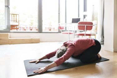 mature woman practicing yoga in childs pose at home