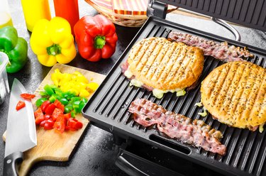 Panini maker with sandwiches and bacon, bell peppers on side on cutting board