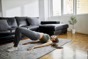 young caucasian woman doing a glute bridge with hamstring curl in her living room