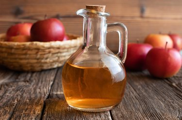 fresh apples and a bottle of apple cider vinegar, as a natural remedy for dandruff