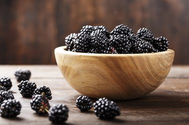 wooden bowl full of fresh blackberries