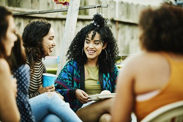 Smiling women sharing food and drinks during backyard barbecue